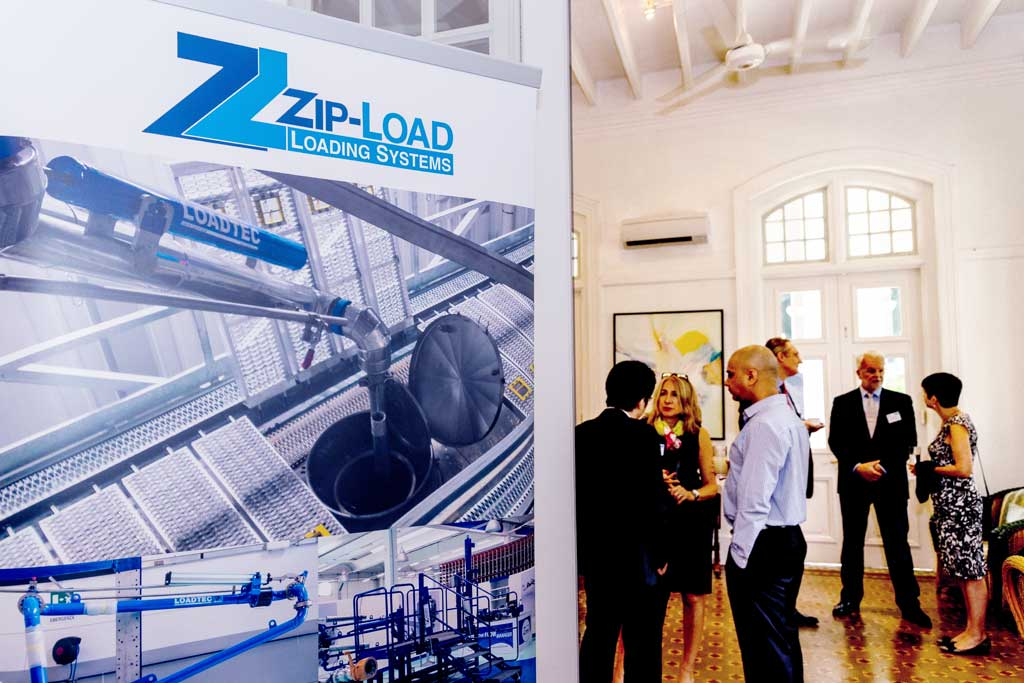 Guests mingling in Eden Hall with Zip-Load banner in foreground